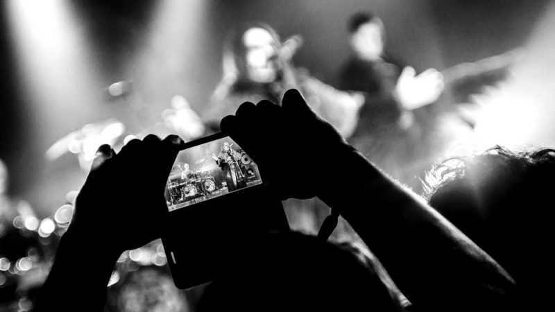 Two hands taking image of singer on a smartphone in the dark black and white
