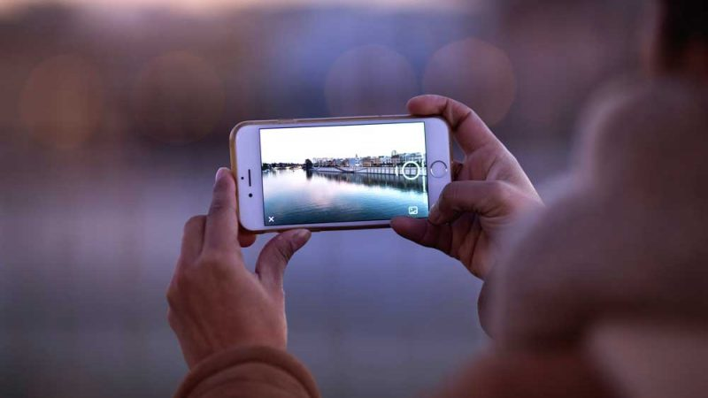 Two hands holding up smartphone to take a beautiful water scenery image