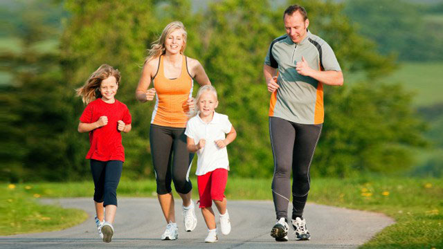 Family of 4 jogging down the road in a park