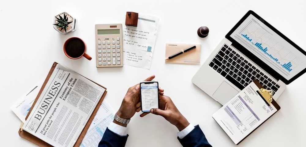 Above visual of a table with laptop and work papers and two hands on a smartphone