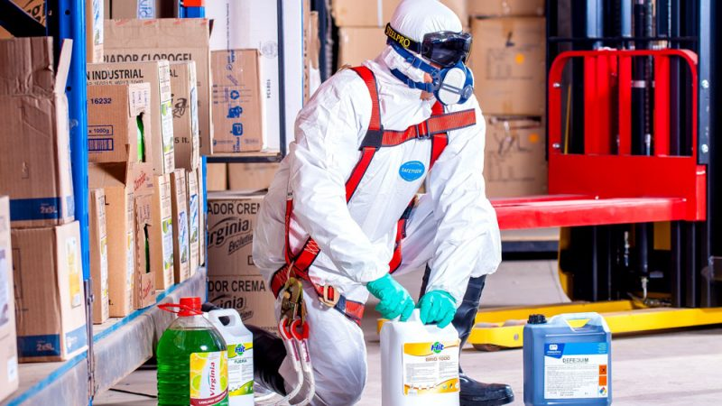 Person dressed in full protective gear opening bottles of chemicals