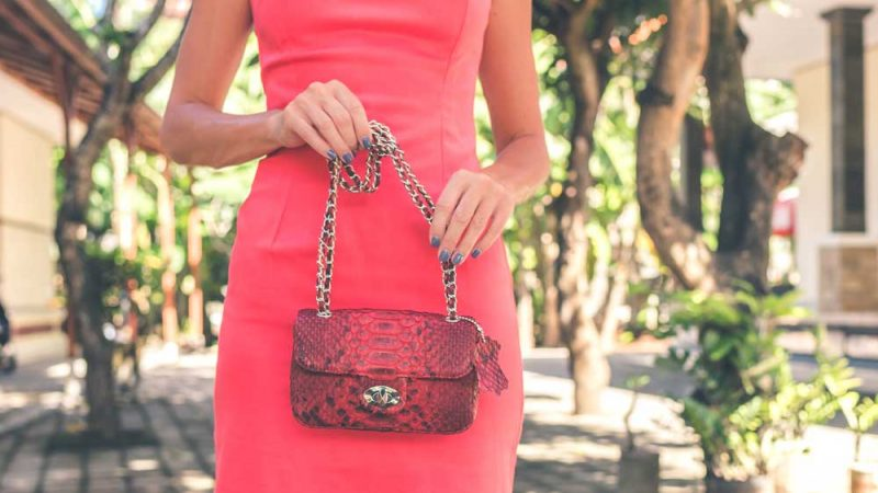 Lady in pink dress outdoors holding a purse
