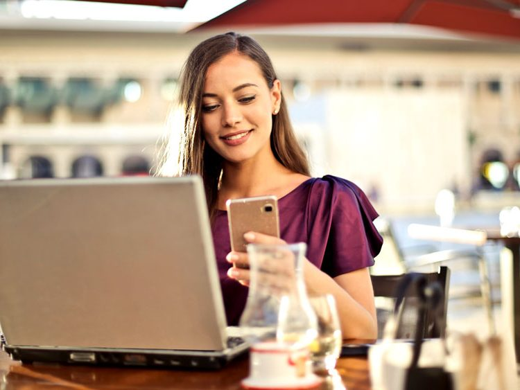 A young women using her laptop and cellphone in a bar or shop while seated at a table