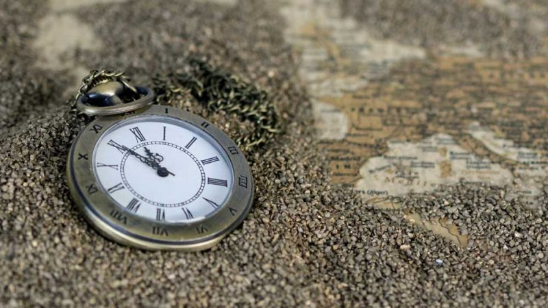 Classical antique clock in the sand near a map