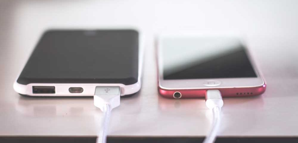 Two phones on a table each being charged with a white charger