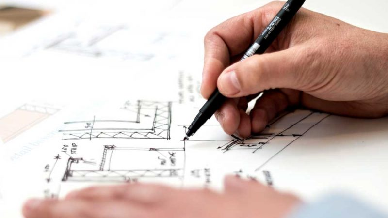 Two hands working on a table drawing architectural plans