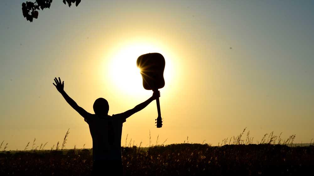 man holding guitar in air facing sun