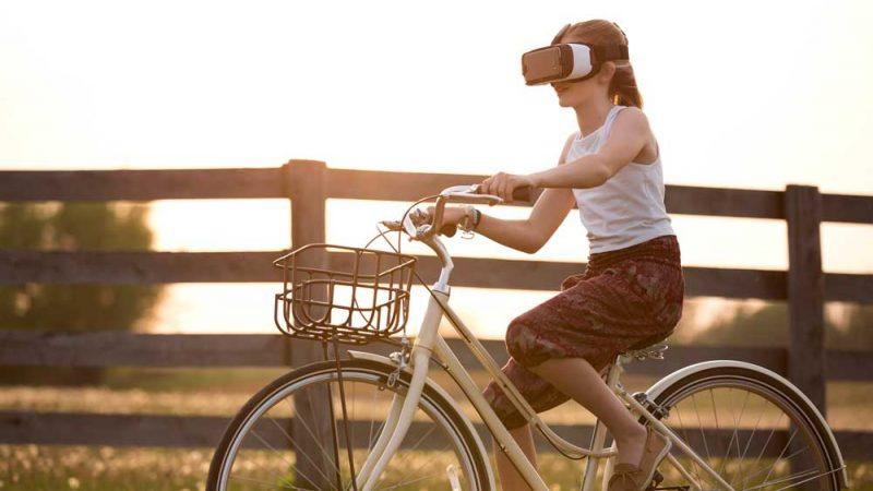 Girl bicycling past a farm fence using VR glasses