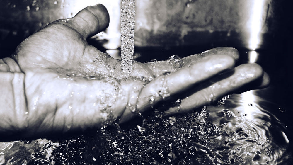Black and white image of a hand close up under falling water likely from a sink