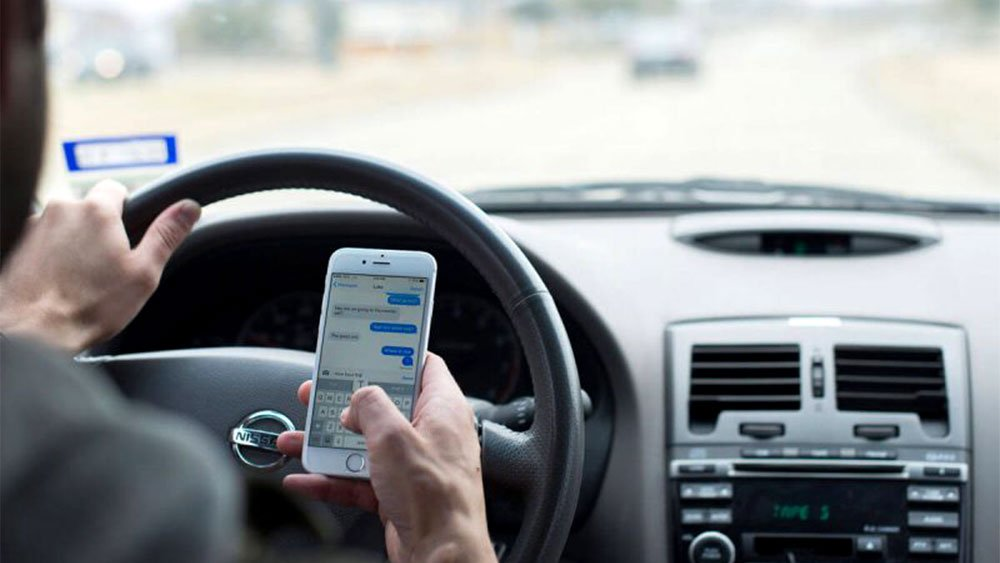 person driving using smartphone