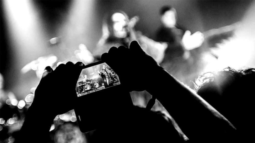 person recording concert with smartphone