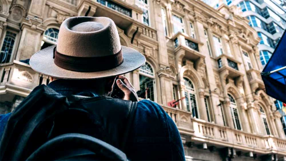 person wearing hat looking at building