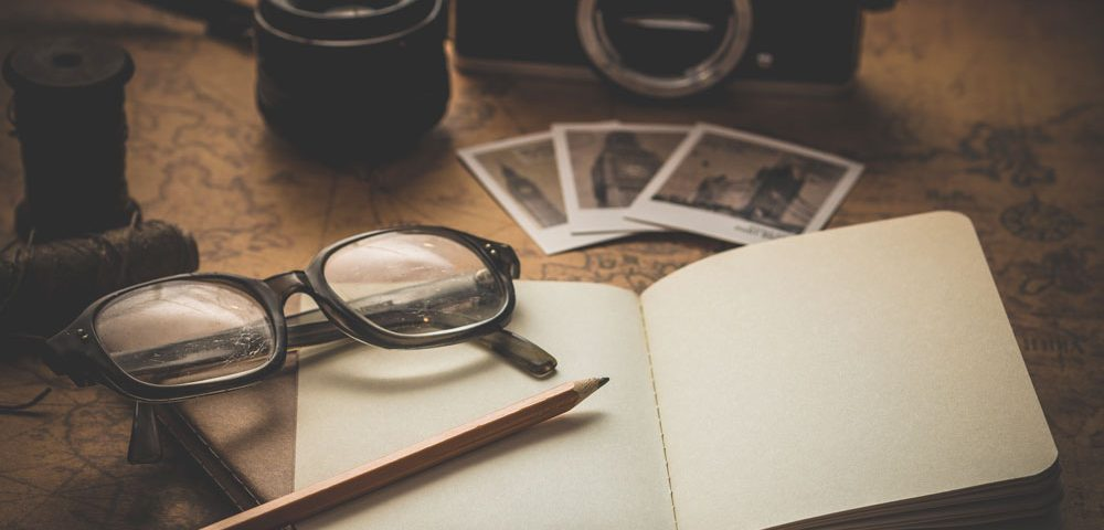 Antiques on a wooden table such as glasses, camera and papers