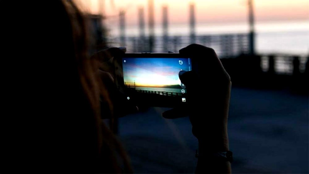 person taking photo with smartphone at dusk