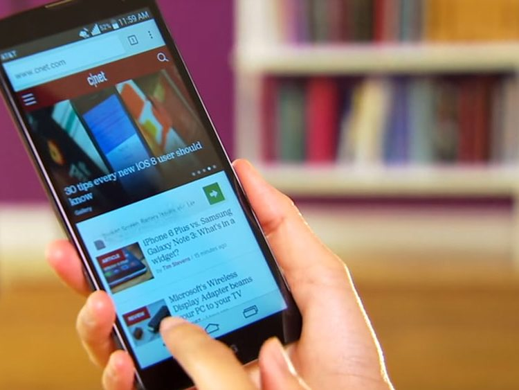 LG G Vista held in hand in front of blurred bookcase