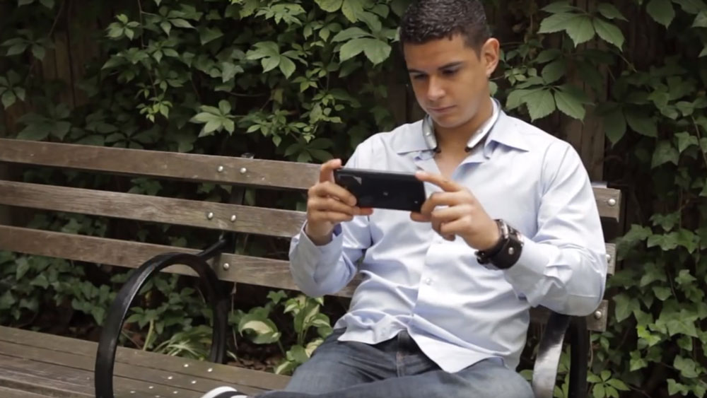 Man watching video on LG G Vista while sitting on park bentch