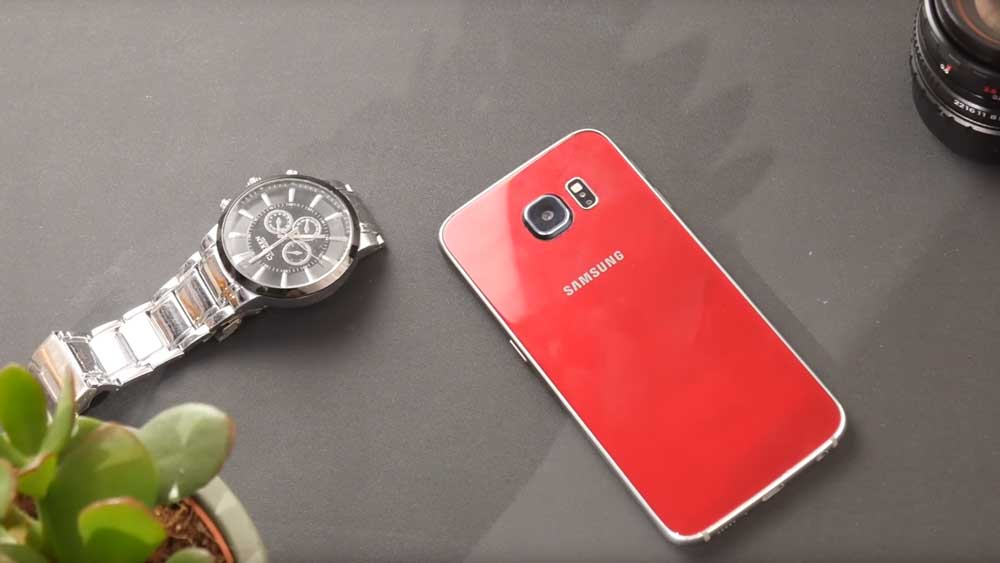 Samsung Galaxy S6 lying on a table near a plant, a watch and a camera lens