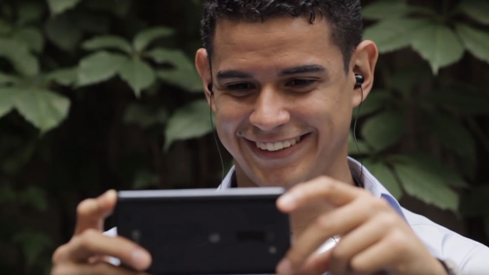 Man smiling while looking at video playing on LG G Vista