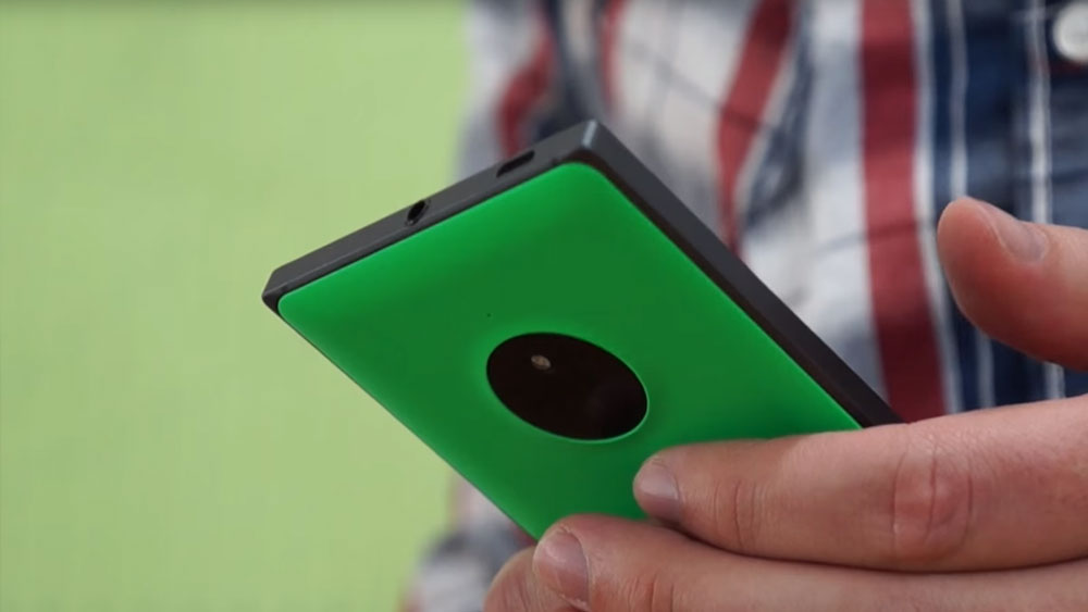 A Man holding the Nokia Lumia 830 and the camera section is seen