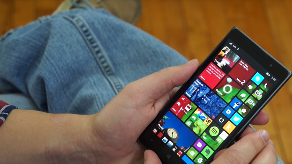 The nokia lumia 830 being held while seated and above a pair of jean pants