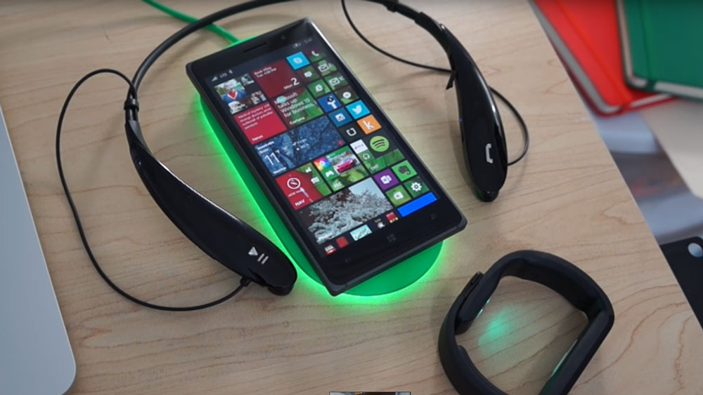 Nokia Lumia 830 Surrounded by headphones on a wooden table