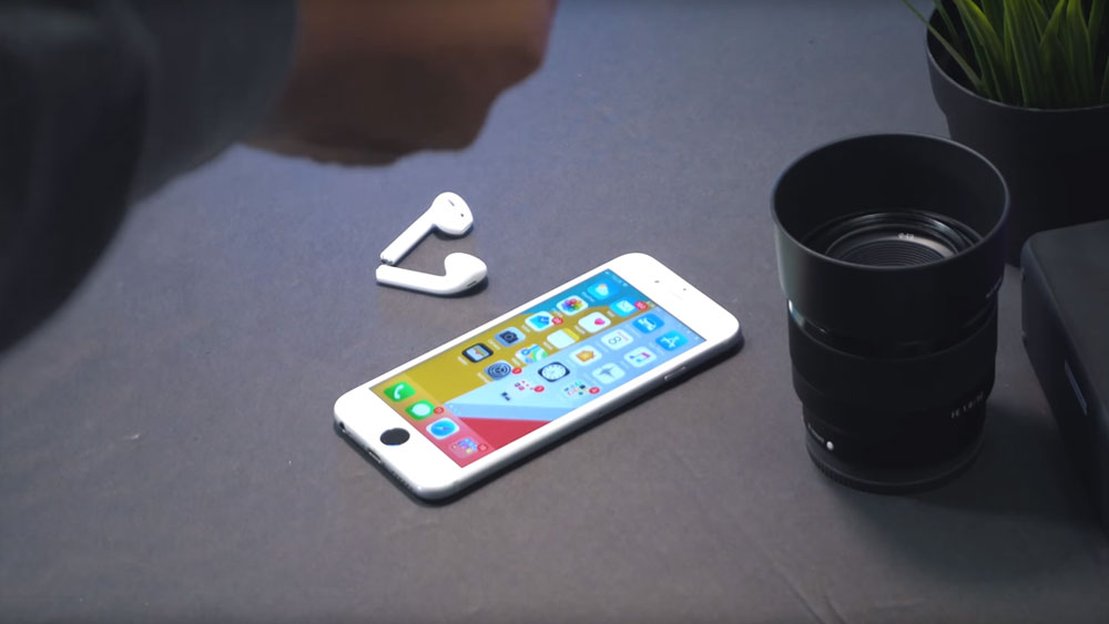 iPhone 6 lying on a table near a headphone set and camera lens