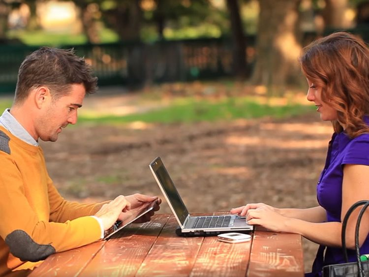 Two people sharing the ZTE Velocity Hotspot while working at a park bench