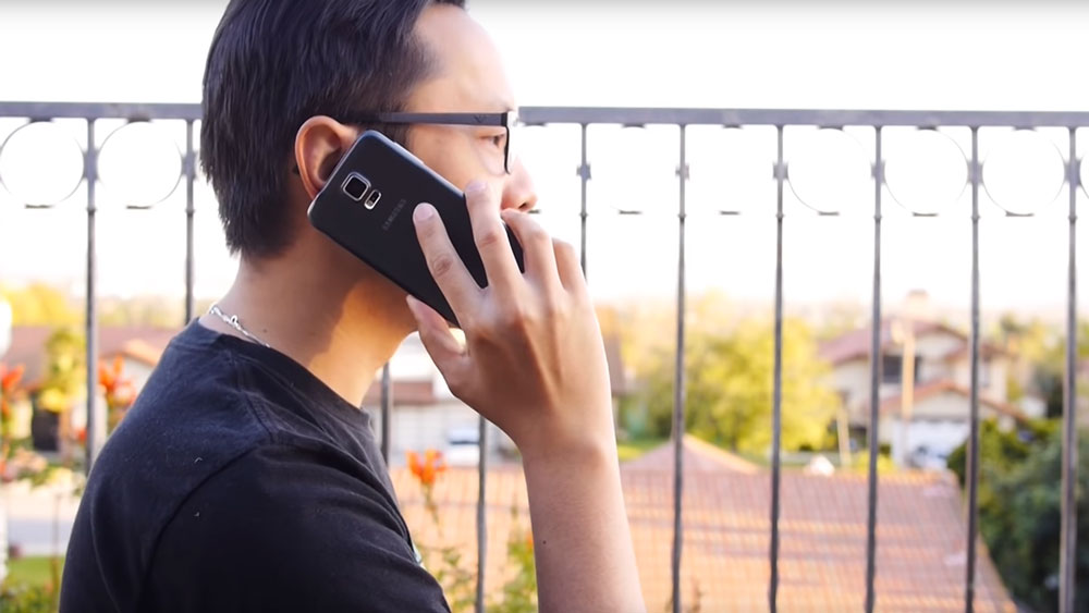Man speaking on a Samsung Galaxy S5 near a porch fence