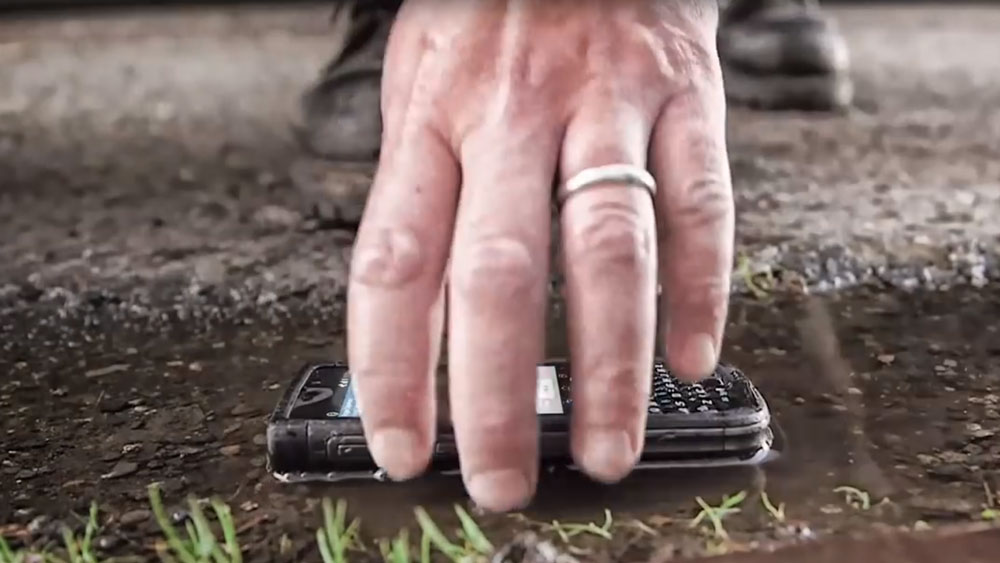 Hand picking up NEC Terrain from a puddle of water