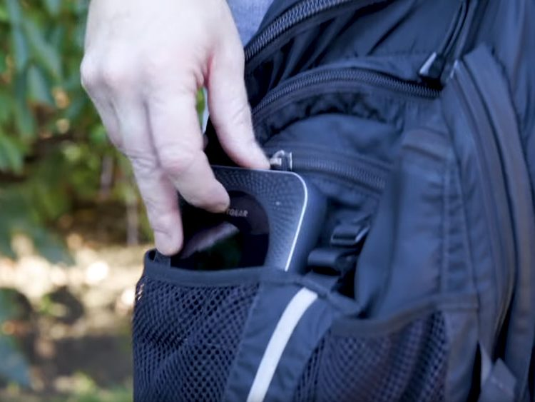 Someone putting the Netgear Nighthawk into a small pocket in camping backpack