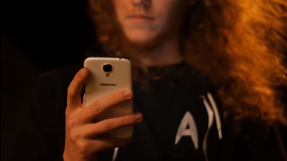 Closeup of man in long orange hair holding the Samsung Galaxy S4