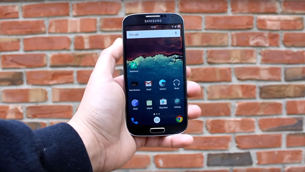 The Samsung Galaxy S4 held in front of a brick wall