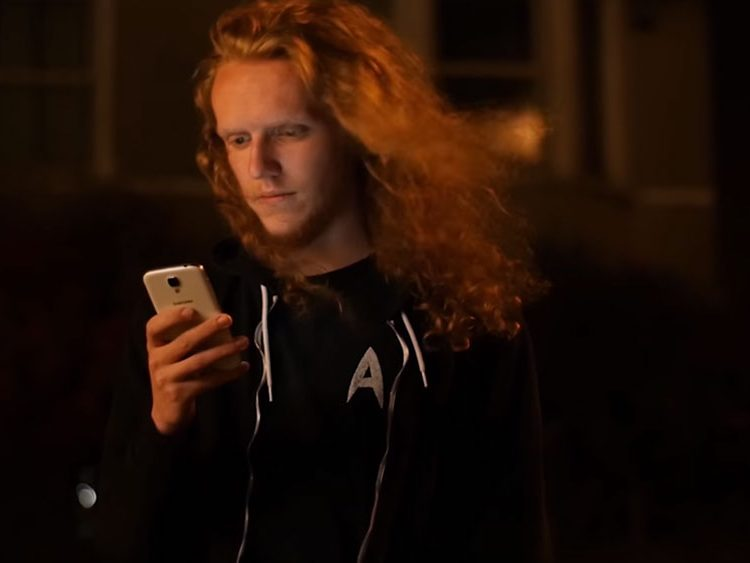 A man with long orange hair holding the Samsung Galaxy S4 in a dark room