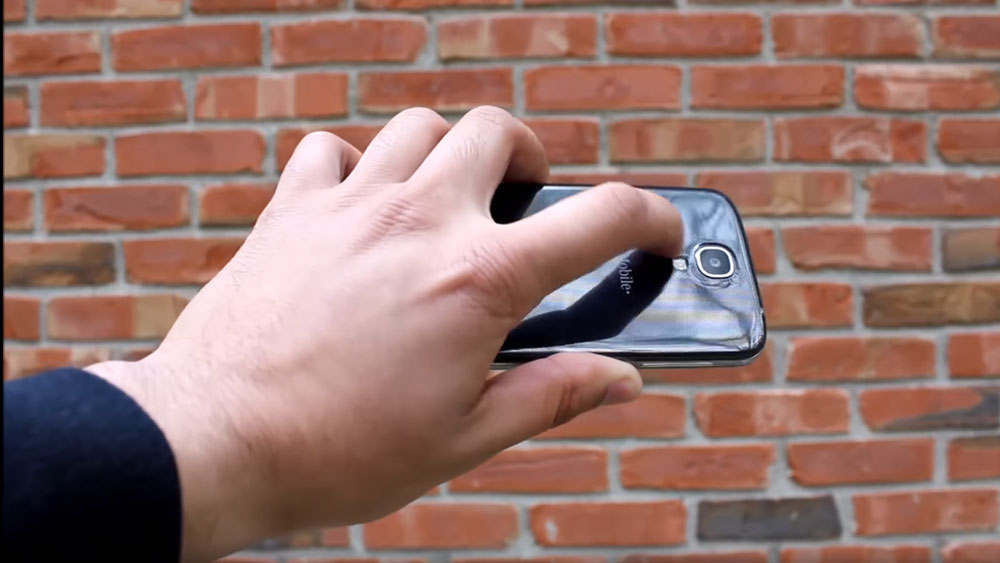 A hand holding the Samsung Galaxy S4 at an angle in front of a brick wall