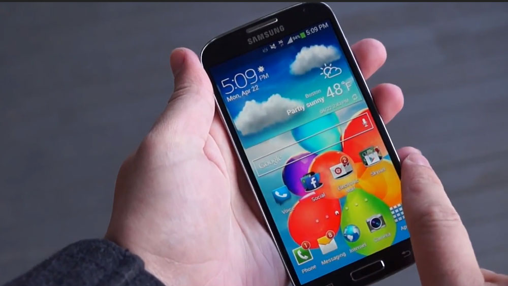 A hand holding the Samsung Galaxy S4 Active showing its front page screen