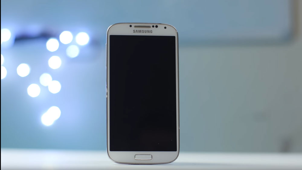 The Samsung Galaxy S4 standing upright in front of bright bokeh