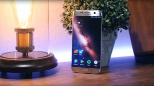 Samsung Galaxy S7 Edge on a table leaning against a plant pot and near a candle