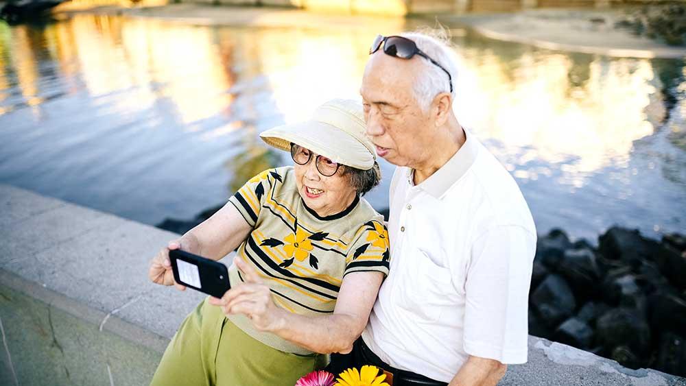 Seniors using phone next to pond
