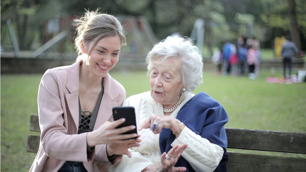 Two women pointing at cellphone on bench