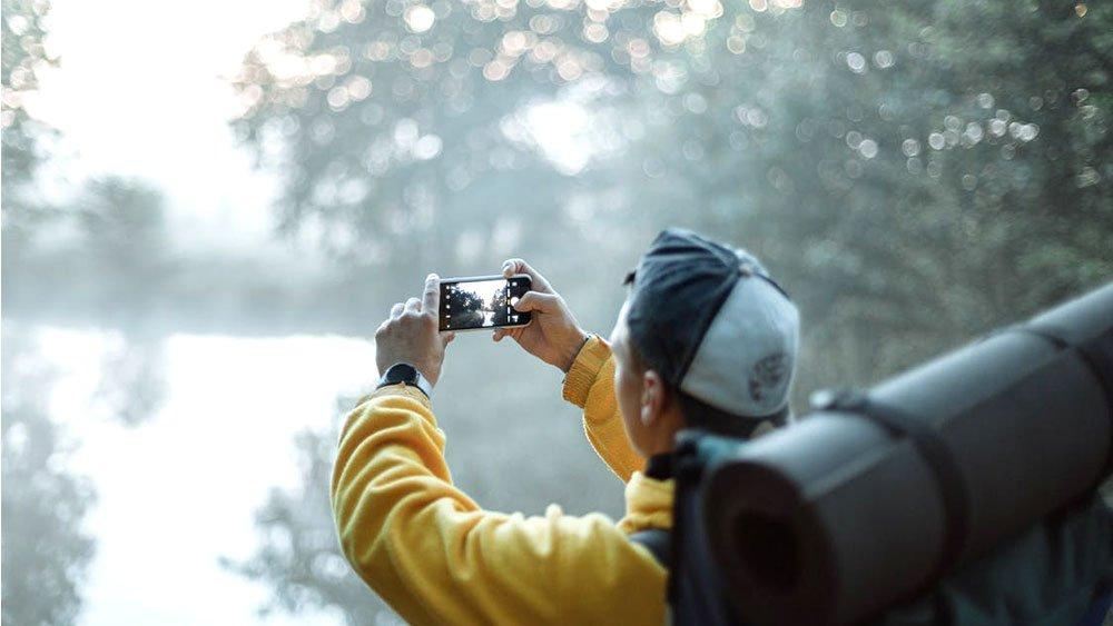 man around trees holding phone taking photo