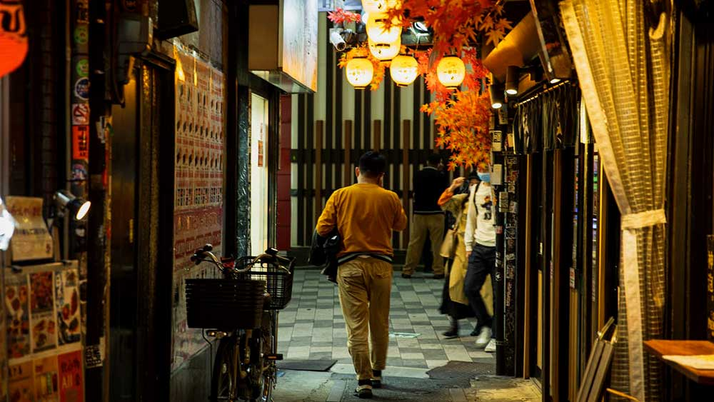 man on phone walking in market