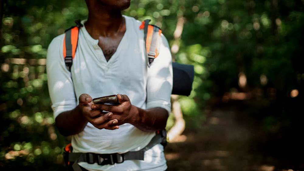 person holding phone on trail