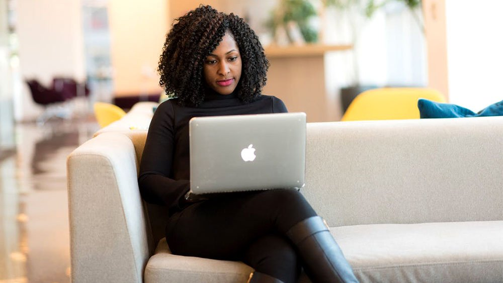 woman sitting on couch using laptop