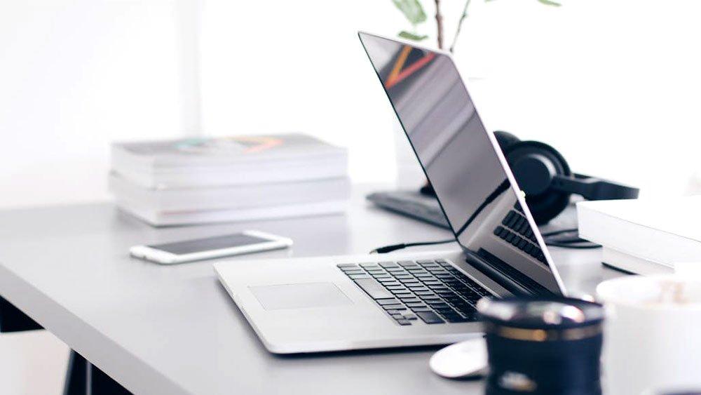 Laptop on desk with phone next to headphones