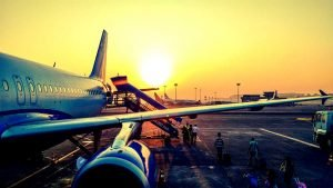 people boarding plane sunset